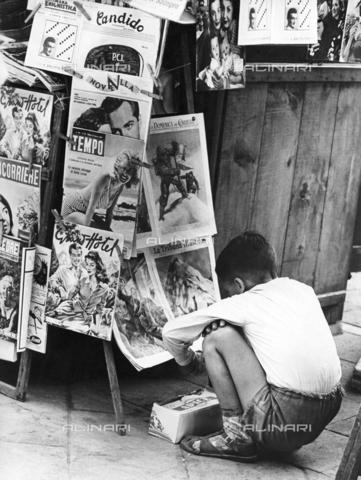 ULL-S-000262-3535 - Child in front of a newsstand - Data dello scatto: 1955 - Oscar Poss / Ullstein Bild / Alinari Archives