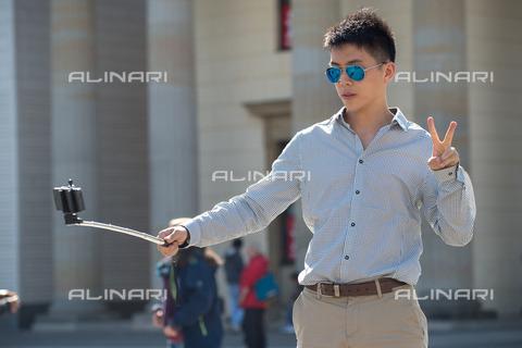 ULL-S-101045-6305 - An Asian boy shooting a selfie front of the Brandenburg Gate in Berlin - Data dello scatto: 07/09/2015 - CARO / Christoph Eckelt / Ullstein Bild / Alinari Archives