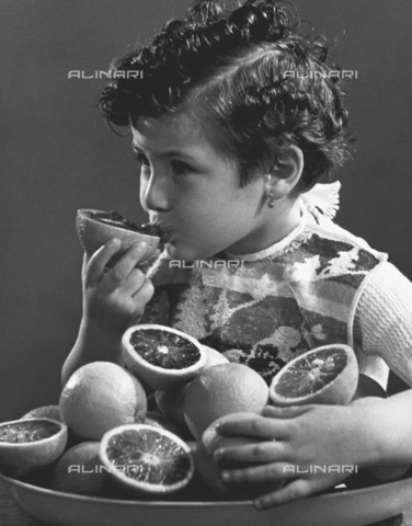 VAA-F-000036-0000 - Photo of a little girl sucking an orange