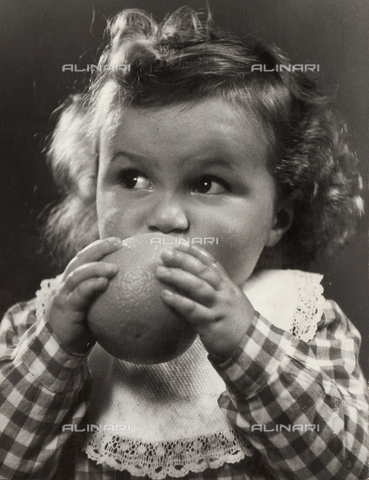VAA-F-000220-0000 - Photo of a little girl taking a bite out of an orange
