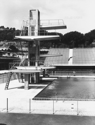 VAA-F-000615-0000 - View of the diving board of an olympic sized swimming pool in a sporting facility. A swimmer is diving in.