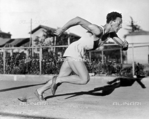 VAA-F-003025-0000 - An athlete on a sandy track during a race. His effort shows his muscle mass.