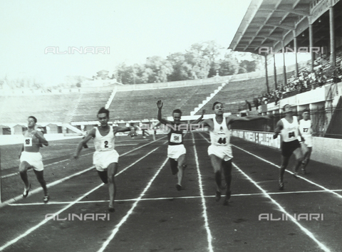 VAA-F-003026-0000 - Athletes crossing the finish line during a race. In the background there is a grandstand full of spectators.