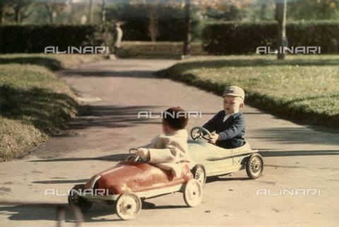 VAA-F-003342-0000 - Coppia di bambini a bordo di un'automobile giocattolo