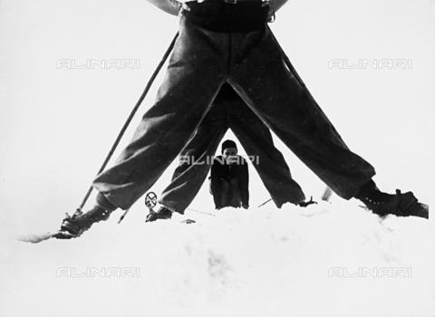 VAA-F-003427-0000 - Sciatore sorridente, è piegato per risultare visibile nell'arco formato dalle gambe divaricate di altri due sciatori. - Data dello scatto: 1940 - 1950 - Archivi Alinari, Firenze