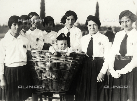 VAA-F-003532-0000 - Group of girls in uniform during the Fascist period standing around a large wicker basket from which a baby wearing a cap is emerging.