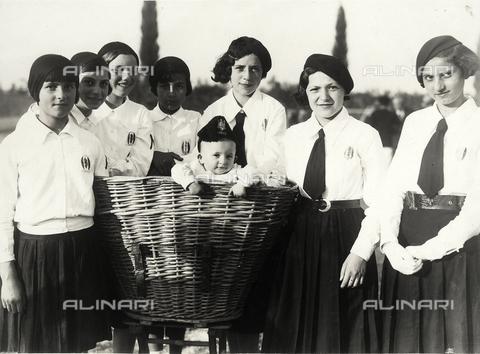 VAA-F-003532-0000 - Gruppo di ragazze in uniforme, durante il periodo fascista, intorno ad una grande cesta di vimini dalla quale sbuca un bambino con un cappello.