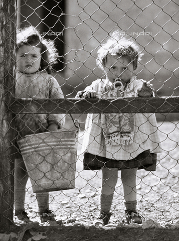 VAA-F-004944-0000 - Two baby girls looking out from behind a fence
