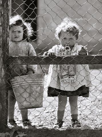 VAA-F-004944-0000 - Due bambine che guardano attraverso una rete