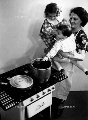 VBA-F-000183-0000 - A smiling woman is holding two children in her arms, she is standing near a gas stove
