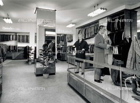 VBA-S-000001-0004 - Interior of a men's clothing shop. In the foreground, to the right, a few manikins with winter coats