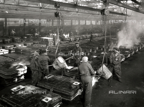 VBA-S-000007-0006 - Interior of an Ideal Standard factory. A few workers, in protective gear, are filling large iron molds with molten metal