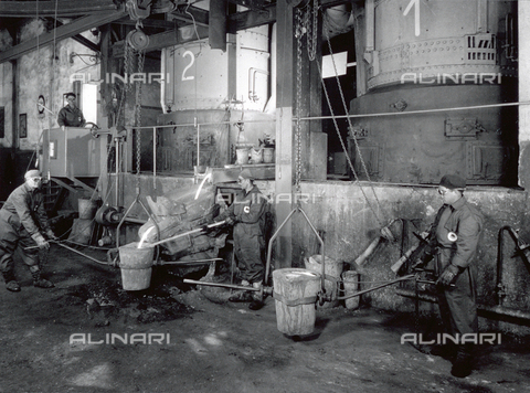 VBA-S-000007-0033 - Interior of a factory of the Ideal Standard plant. A few workers in protective gear are working with molten metal