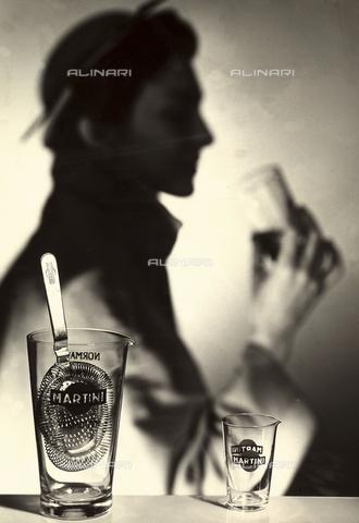 """VBA-S-000032-0002 - Pubblicità per il vermouth """"Martini"""". In primo piano due bicchieri vuoti con il marchio e l'iscrizione della celebre bevanda, in uno di essi è inserito l'utensile per la preparazione di cocktail. Sullo sfondo, è visibile l'ombra di una figura che tiene un bicchiere in mano. - Data dello scatto: 1950- 1959 - Archivi Alinari, Firenze"""