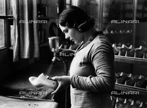 VBA-S-000111-0003 - Calzaturificio Marzocchi di Bologna: operaia durante una fase di lavorazione su una forma da scarpa - Data dello scatto: 1930 - Archivi Alinari, Firenze