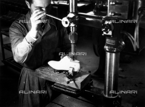 VBA-S-000111-0006 - Shoe Marzocchi Bologna: snapshot of the interior of the shoe factory. In the foreground a worker adjusts a wooden mould