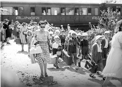 VBA-S-000234-0001 - Snapshot of the arrival at a station of a large group of children from a summer camp. The children, who are accompanied by some adults, have just left the train