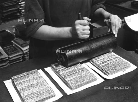 VBA-S-000238-0030 - L'immagine, ripresa in una tipografia, mostra il passaggio manuale di un rullo su tre blocchi di composizione di caratteri - Data dello scatto: 1930 ca. - Archivi Alinari, Firenze