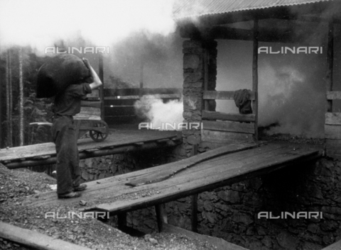 VBA-S-000255-0001 - Snapshot taken of an openpit mine. In the foreground a miner carries a heavy sack over his shoulder