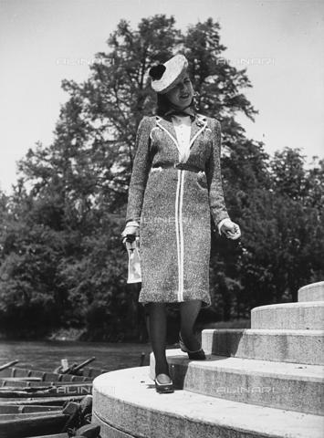 VBA-S-000466-0019 - Modella posa sorridente in riva a un lago, indossando un cappotto di lana e un cappello con pompon - Data dello scatto: 1930 - Archivi Alinari, Firenze