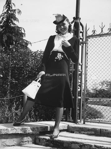 VBA-S-000466-0022 - Una modella sorridente posa davanti a un cancello: indossa un tailleur con gonna svasata e bolerino su camicia bianca. Sulla testa porta un cappellino originale - Data dello scatto: 1930 - Archivi Alinari, Firenze
