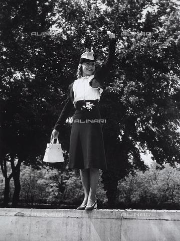 VBA-S-000466-0027 - Una modella sorridente saluta in piedi su un muretto: indossa un tailleur con gonna svasata e bolerino su camicia bianca. Sulla testa porta un cappellino originale - Data dello scatto: 1930 - Archivi Alinari, Firenze