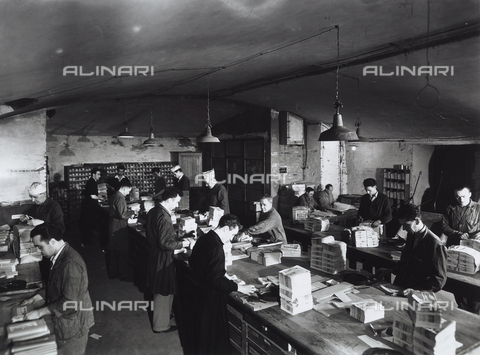 VBA-S-000813-0017 - Interior of a newspaper warehouse where numerous workers prepare bundles of newspapers to be distributed