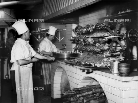 VBA-S-001396-0002 - Cuochi al lavoro nella cucina di un ristorante. In primo piano, il cuoco addetto alla cottura dei polli allo spiedo. - Data dello scatto: 1958 - 1968 - Archivi Alinari, Firenze