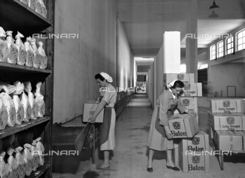 VBA-S-002259-0006 - Snapshot of the distillery Buton warehouse where two women workers are placing boxes of spirits on a conveyor belt
