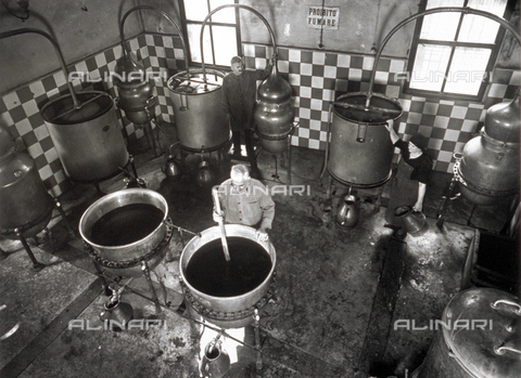 VBA-S-002259-0009 - View from above of a room in a distillery, where three elderly workers are working around a few simple direct heat alembics