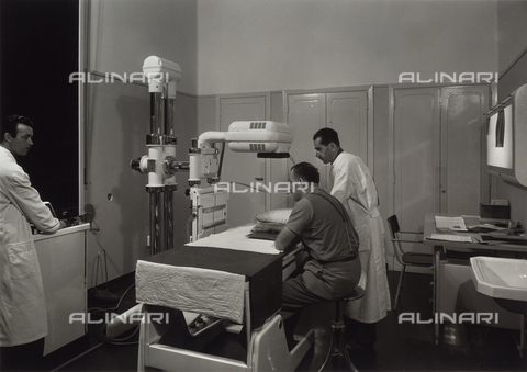 VBA-S-002276-0037 - INAIL of Parma. Two doctors preparing a patient for a radiological exam on his arm.
