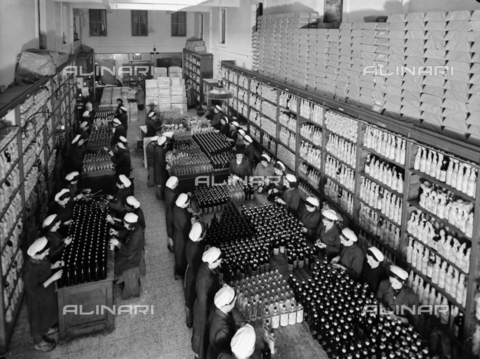 VBA-S-002511-0003 - View rom above of a distillery warehouse. Numerous women workers around tables are packing the bottles for shipping