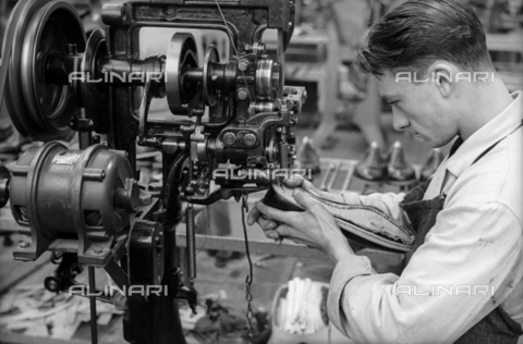 VBA-S-003975-0003 - Closeup of a young worker to sew a shoe with the help of a machine inside the shoe factory Montanari