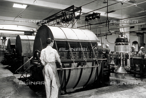 VBA-S-004347-0035 - Interior of an industrial brewery. In the foreground a worker next to machinery for the washing and filling of the bottles. In the background a few women workers can be seen