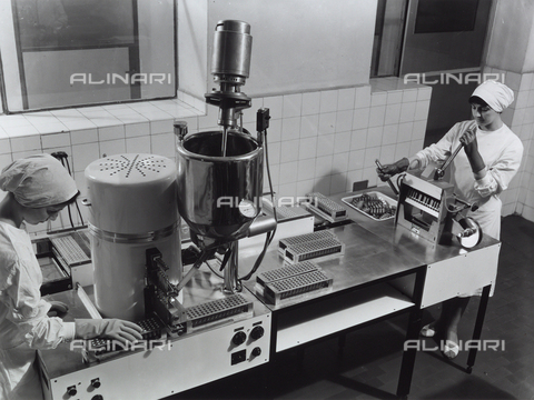 VBA-S-004674-0343 - Two workers at a machine for packaging medicinal suppositories at the Recordati pharmaceutical factory.