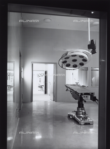 VBA-S-005427-0002 - General Hospital. Photograph of an operating room with a bed and an overhead lamp.