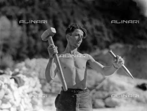 VBA-S-007060-0270 - Laconi Cave: Photograph of a bare-chested worker with mallet and a chisel. The photograph was commissioned by the ILVA factory of Genoa.
