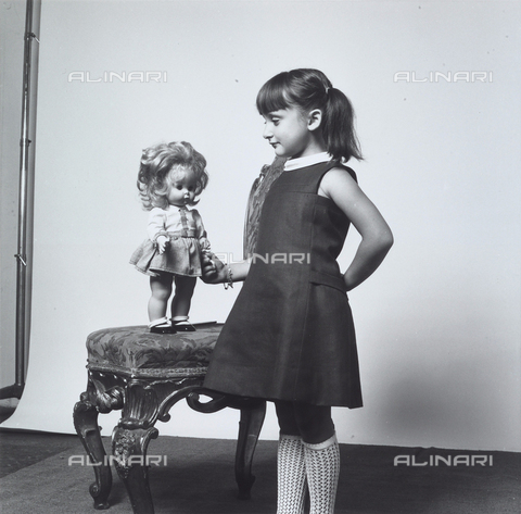 VBA-S-009741-0009 - Portrait of a young girl posing in profile with a doll standing on a chair.