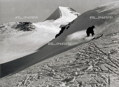 VBA-S-010507-0005 - A snow-covered mountain landscape. In the distance a skier goes by. In the foreground: the ski tracks that have passed over the untouched surface of the snow