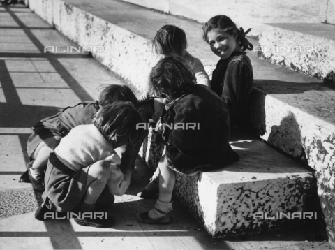 VBA-S-010508-0002 - A group of children playing in the street, sitting on some steps.