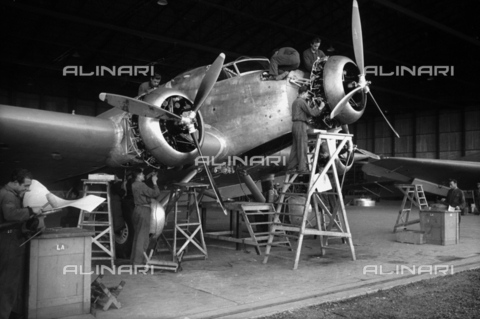 VBA-S-012200-0252 - A group of technicians building an airplane inside a hangar of Caproni factory