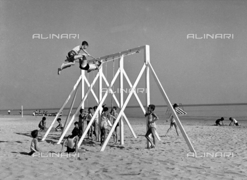 VBA-S-049150-0002 - A group of children playing on a swing on the beach