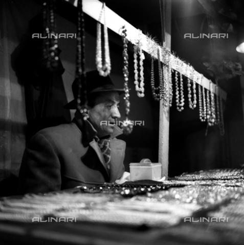 VBA-S-050750-0008 - Un venditore di articoli di bigiotteria serve un cliente all'interno di un mercato coperto - Data dello scatto: 1940 - 1950 - Archivi Alinari, Firenze
