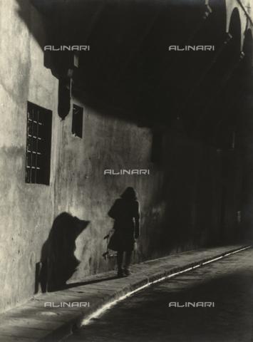 """VZA-F-000285-0000 - """"Ritorno"""". Donna che cammina su un marciapiede di notte - Data dello scatto: 1950 - 1955 ca. - Raccolte Museali Fratelli Alinari (RMFA)-archivio Vannucci Zauli, Firenze"""