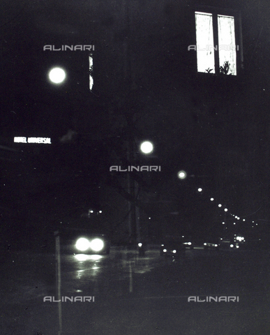 "VZA-F-000299-0000 - ""Window in the night"". View of a street at night with street lights and cars; It is also known the luminous sign of a motel and a lighted window - Data dello scatto: 1980 - Archivi Alinari, Firenze"