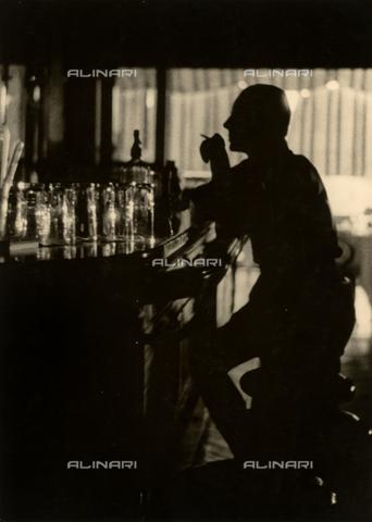 """VZA-F-000323-0000 - """"Imbruna"""". Profilo di uomo in controluce seduto davanti al bancone di un bar - Data dello scatto: 1950 - 1955 ca. - Raccolte Museali Fratelli Alinari (RMFA)-archivio Vannucci Zauli, Firenze"""