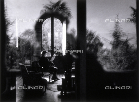 "VZA-F-000361-0000 - ""The house in the country."" A woman is visible seated on an armchair in a parlor, reading a magazine - Data dello scatto: 1940 ca. - Archivi Alinari, Firenze"