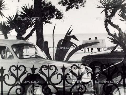 VZA-F-000465-0000 - Benches on the promenade.  View though a gate of the waterfront with cars and two men sitting on a bench - Data dello scatto: 1950-1960 ca. - Archivi Alinari, Firenze