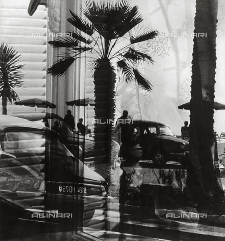 """VZA-F-000470-0000 - """"Finestra sulla Promenade des Anglais"""". Veduta del lungomare di Nizza con automobili, palme e persone che passeggiano o sotto gli ombrelloni - Data dello scatto: 1950-1960 ca. - Raccolte Museali Fratelli Alinari (RMFA)-archivio Vannucci Zauli, Firenze"""
