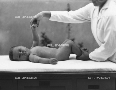"""WWA-F-001950-0000 - Nurse with newborn during an exercise for the book """"La ginnastica del lattante"""" (Infant Exercises) by Eugenio Paulin"""